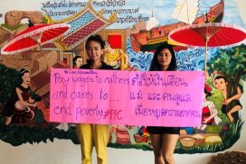 Two Southeast Asian women hold a banner in English and Thai