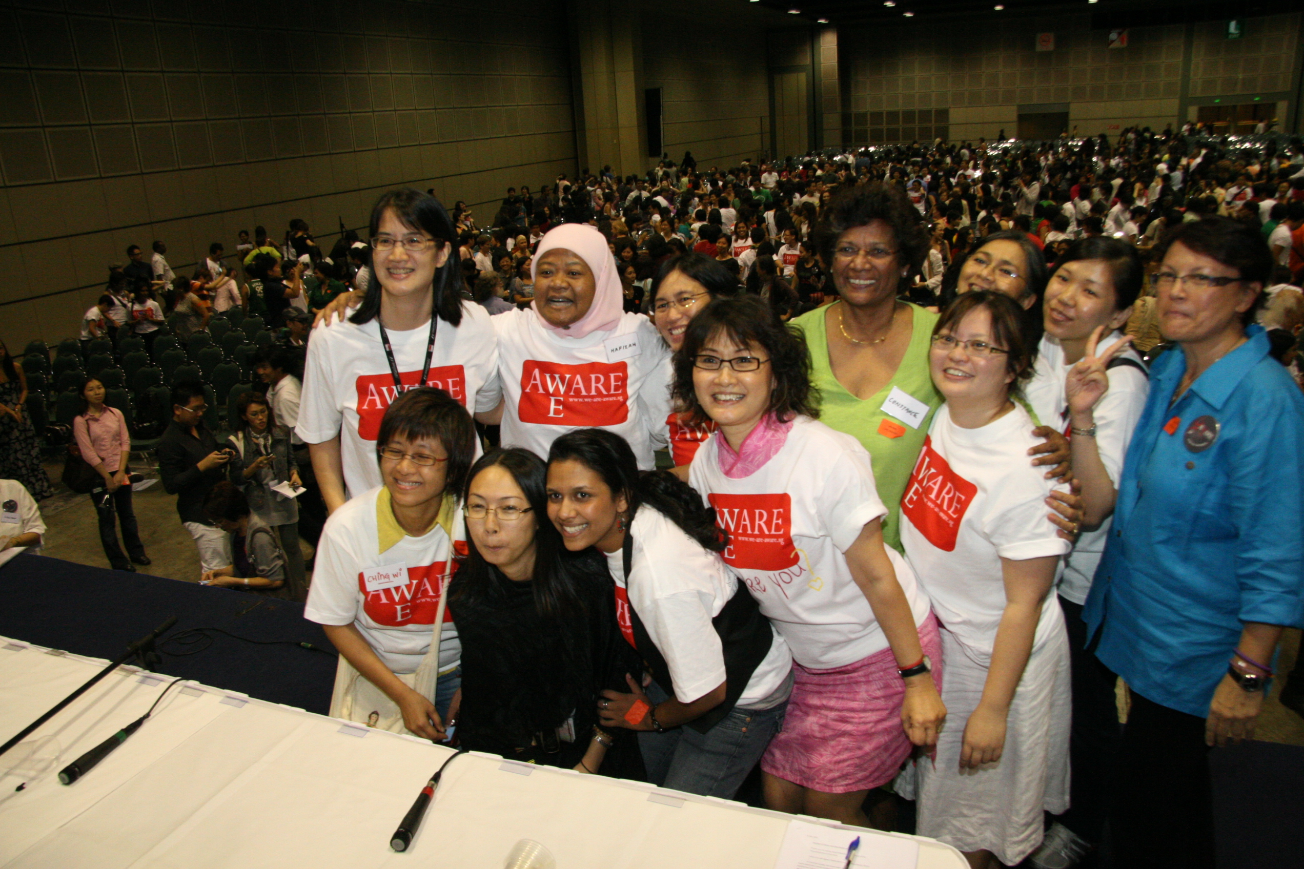On the left, a group of women pose together facing the camera. Oot is seated in the middle of them wearing a tiara. On the right, Oot stands to the right of another woman, head tilted and smiling cheekily at the camera.