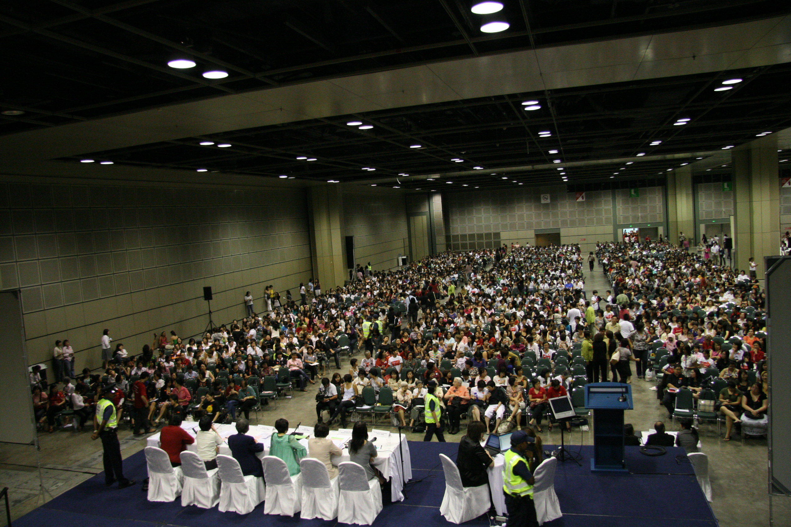 On the left is someone holding four cards in their hand. The text on the cards are in Thai and English. The top card reads 'Cocaine'. On the right, a group of people are looking through a large pile of cards that have been spread out on the floor.
