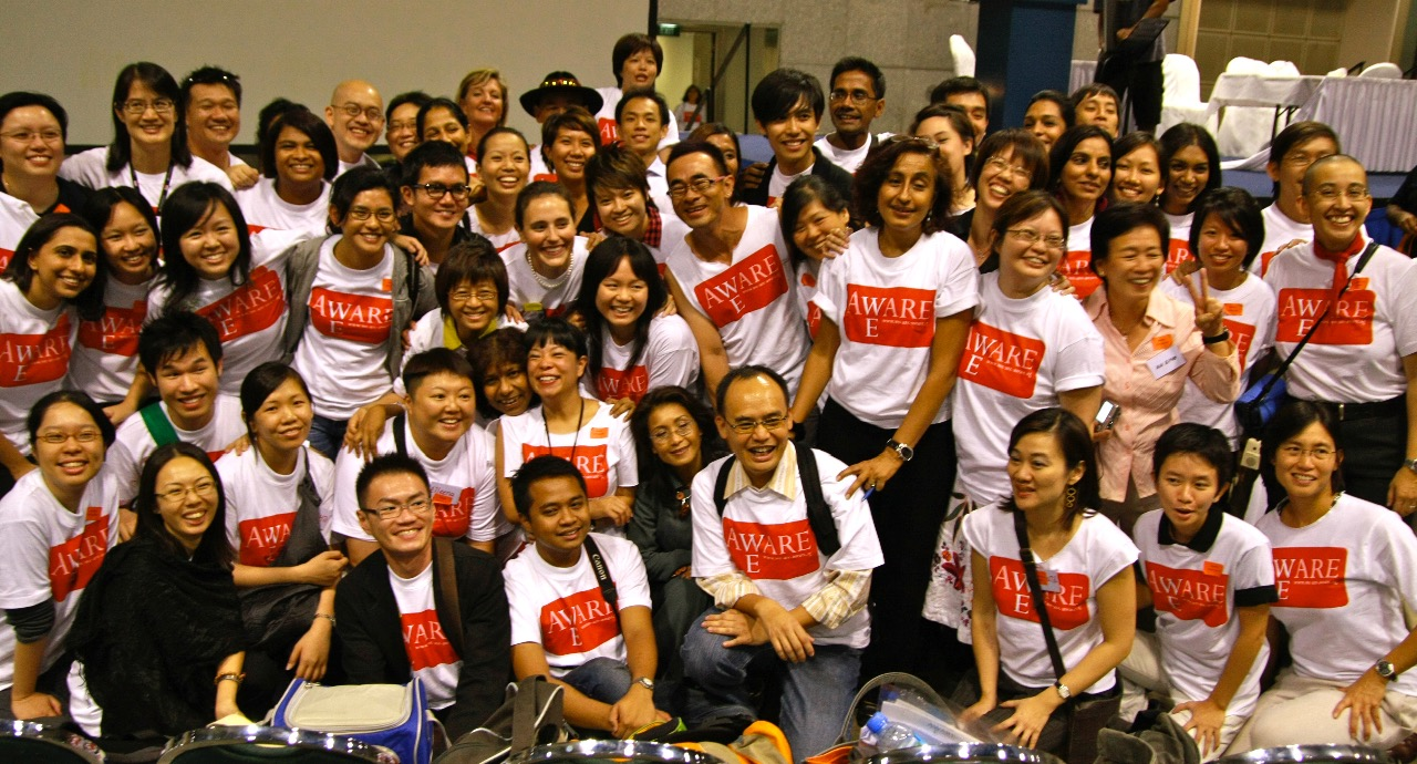 A group of participants pose together in a room, some are standing while others are kneeling. A few of them are holding tote bags.